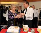 Admiral Zambellas presents a decanter to Peggy Caren