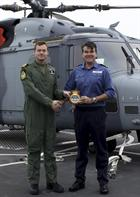 CO 700W Lt Cdr Simon Collins gives squadron crest to Dragon's CO Captain Ian Lower