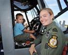 Lt Danielle Welch a student on 702 NAS with a young visitor in the pilot's seat of a Lynx HMA Mk8