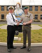 Commander Terry Tyack and Corps RSM, RSM Ally McGill handing over the RSM's Cane