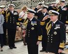 The new First Sea Lord Admiral Sir Philip Jones (centre) salutes on board HMS Victory