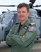 Commodore Nicolas Tindal, the new Commanding Officer of RNAS Yeovilton in front of a Wildcat helicop