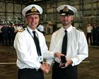 Rear Admiral Keith Blount presents Lieutenant Commander Chris Grey with his LSGC medal for 17 years