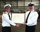 Rear Admiral Keith Blount presents Warrant Officer Paul Roe with Royal Warrant Parchment