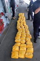 The bales of heroin seized from the dhow lined up on the deck of HMS Westminster