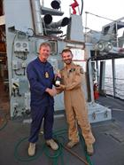 Captain Nick Hine presents Petty Officer (Air Crewman) Leigh Williams with a bottle of champagne