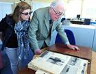 Sue Pooley and Capt Howard DSC looking through press cuttings from his time at Culdrose